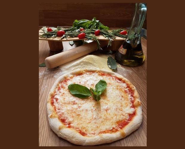 Pizza margarita. Precocinada a la piedra y aliñada con pulpa de tomate y albahaca fresca .