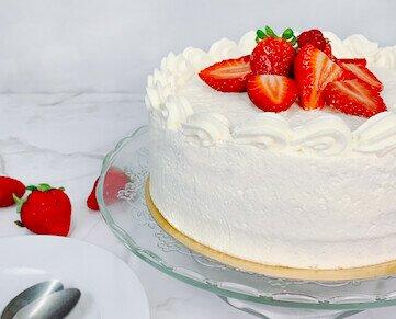 Tarta de nata y fresas. Un bizcocho de vainilla ligero, con una capa de crema pastelera, envuelto por nata.