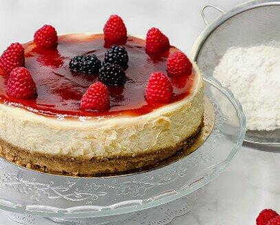 Tarta de queso y frambuesa. Capa de mermelada de frambuesa acompaña la propia fruta sobre una tarta de queso